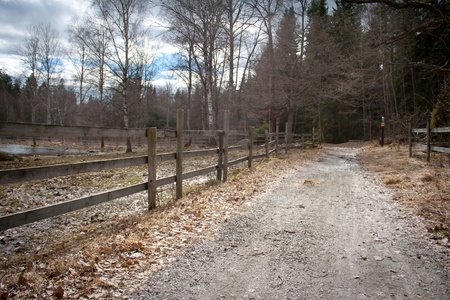 Wooden fence along a gravel path Stock Photo