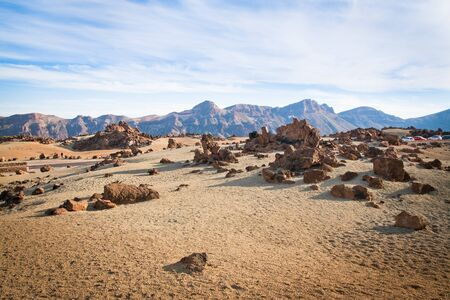 A spot in Tenerife with many rocks and a beautiful mountain landscape in the background