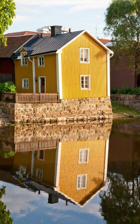 A reflection of a yellow house near Arboga river, Sweden Stock Photo - 10023451