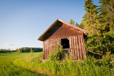 A red barn on a field next to the woods Stock Photo - 10089616