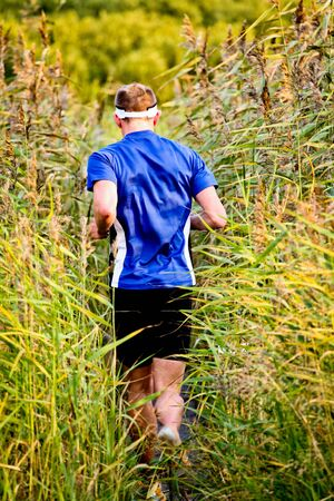 A man running through reed in nature
