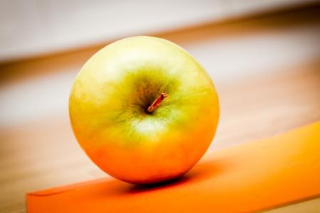 A green apple lying on an orange paper