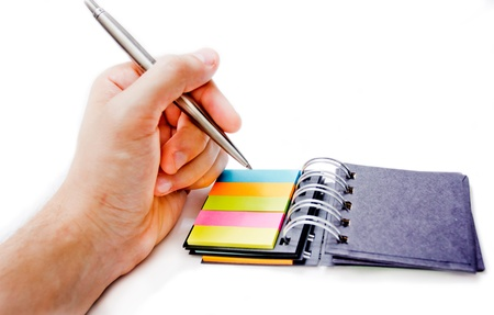 A hand writing with a pen on a coloured note