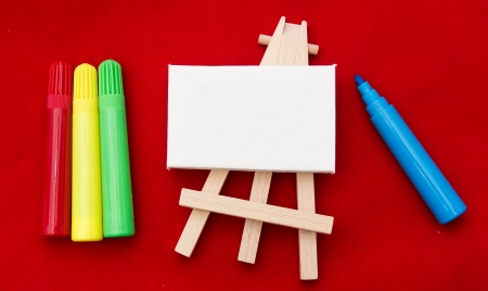 Coloured pens lying beside a wooden easel with an white empty area Stock Photo