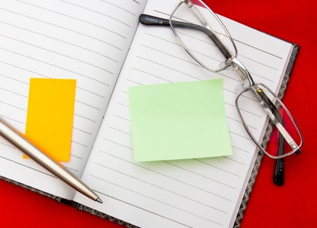 Glasses and a pen lying on a note together with coloured post it Stock Photo
