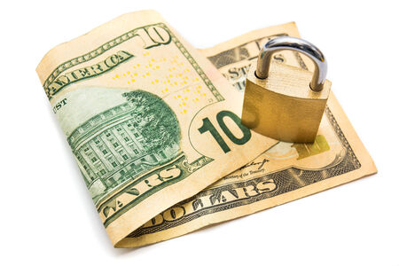 A padlock on top of a 10 dollar note isolated on white background Stock Photo