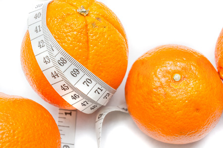 Measuring tape around a oranges isolated on white background