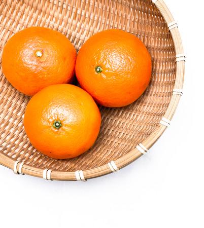 Three oranges lying inside a net basket, isolated on white background Stock Photo