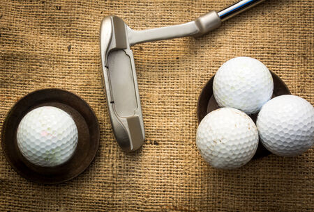 Golf balls lying on metal plates next to a putter Stock Photo