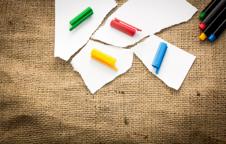 Four white paper pieces decorated with four different colours photo