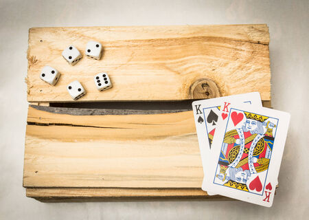A pair of kings together with dices on a wooden support