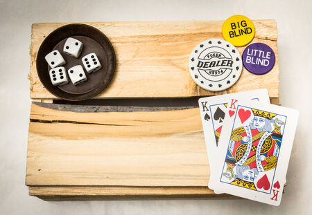 A pair of kings together with dices and a dealer button on a wooden support