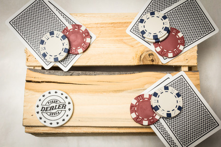 Playing cards lying on a wooden support together with dealer and blind buttons