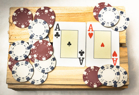 A pair of aces together with a pile of chips on a wooden support