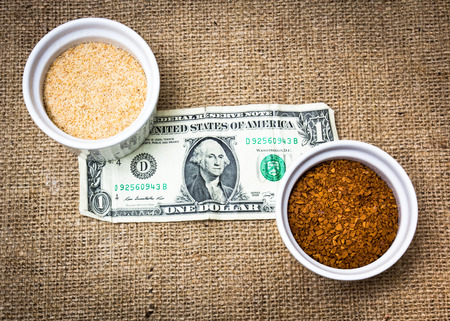 Various type of ingredients poured in several porcelain cups together with a dollar bill Stock Photo