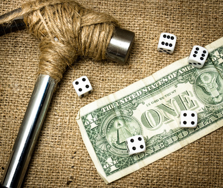 A hammer stopped from destroying money together with dices