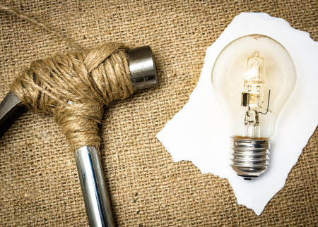 destroying: A hammer stopped from destroying a lightbulb