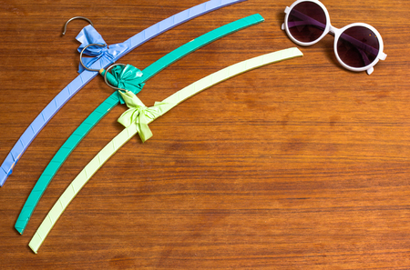 Sunglasses and colourful vintage hangers on wooden teak Stock Photo