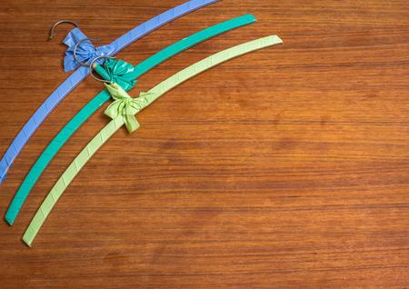 Three colored vintage hangers on wooden teak
