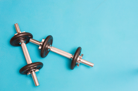 Two dumbbells isoloted on lue background Stock Photo