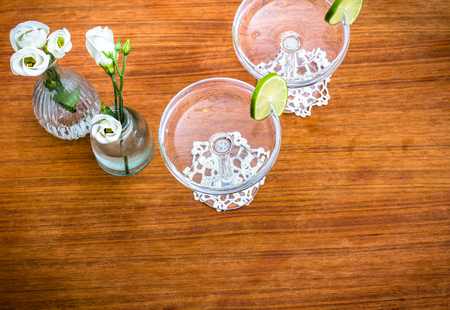 Two glasses and two vaves with flowers on wooden teak table