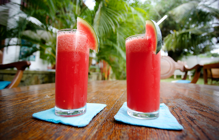 Two glasses with crushed watermelon inside standing on a wooden table