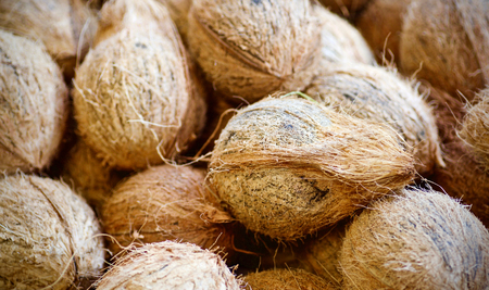 Many coconuts with shells lying in a big basket