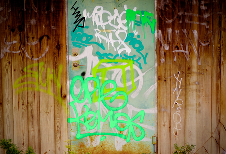 Door and wooden wall covered in grafitti