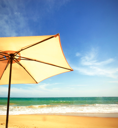 A parasol on the beach in front of the ocean waves on Sri Lanka