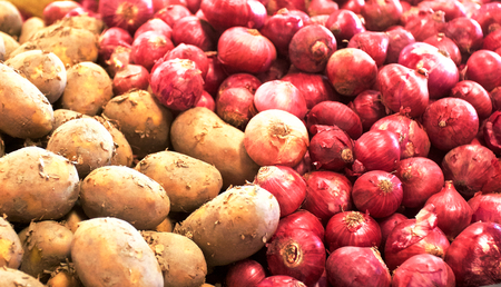 Potatoes and red onions lying next to each other in a basket Stock Photo