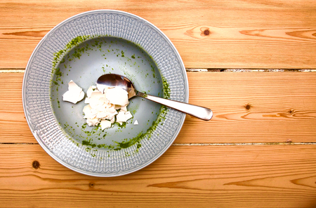 Broccoli soup rests on a plate with eggshell and spoon.