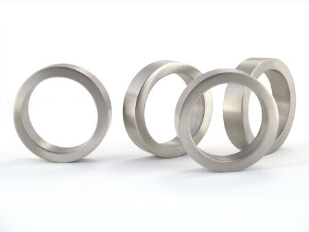 Four Brushed Metal Rings; Concept: Odd man out. Isolated; macro