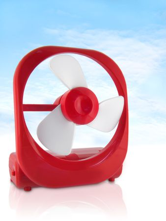 Small Red Personal Fan against light blue sky; macro