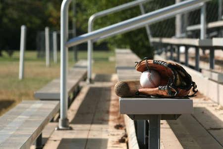 Guante de béisbol, pelota y bate a los bancos vacíos  Foto de archivo - 2447942