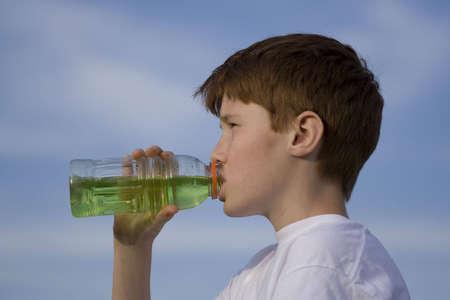 Boy drinking sport drink photo