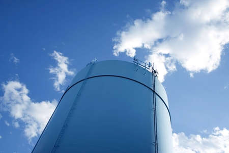 fuel tank: Cylindrical storage tower over blue sky