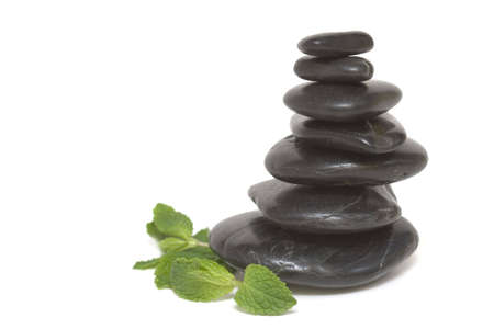 Pebble tower  with mint leaves isolated over white photo