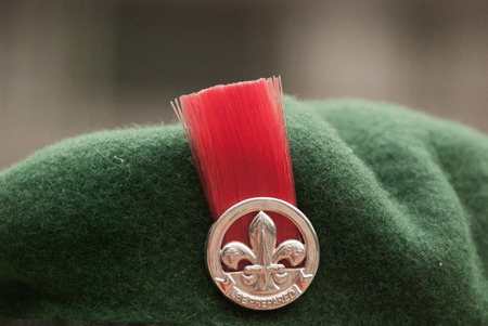 Red badge on beret of boy scout, Hong Kong, China photo