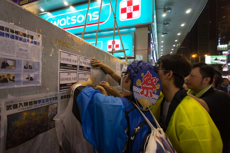 posting: Protester posting poster on Nathan road, a street blocking demonstration in 2014, Mong Kok, Hong Kong, China Editorial