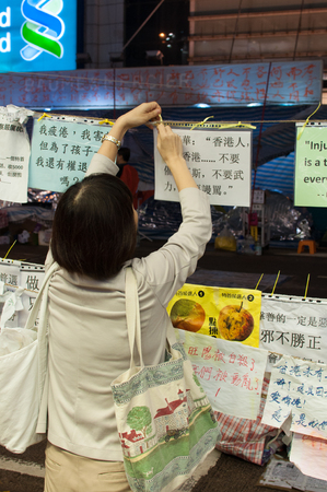 protester: Protester fixing poster, a street blocking demonstration in 2014, Causeway bay, Hong Kong, China