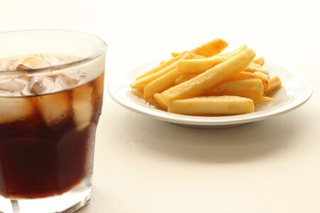 Glass of cola and fried potatoes on plate photo