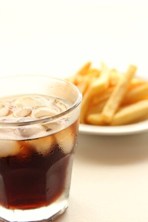 Glass of cola and fried potatoes on plate