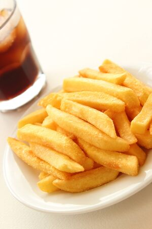 Fried Potatoes on plate and glass of cola