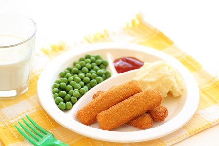 Fish fingers, mushed potato and green-peas on plate photo