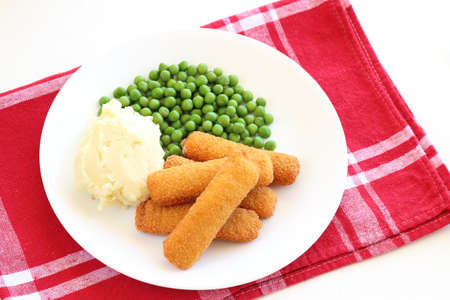 Fish fingers, mushed potato and green-peas on plate