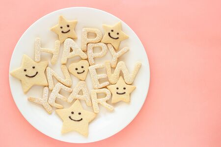 Happy new year homemade cookies on pink background photo