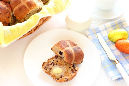 toasted hot cross bun with butter on plate