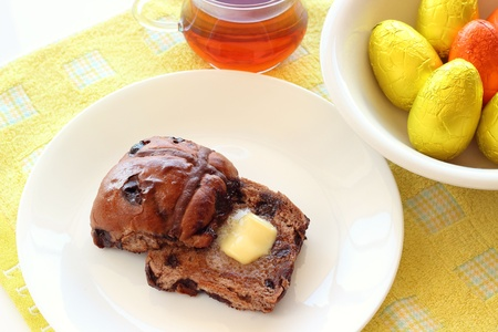 Chocolate hot cross buns with butter and easter eggs for easter table Stock Photo