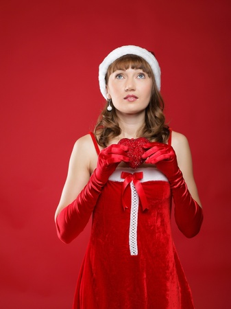 Young charming girl dressed as Santa holds a gift in the form of heart in his hands. photo