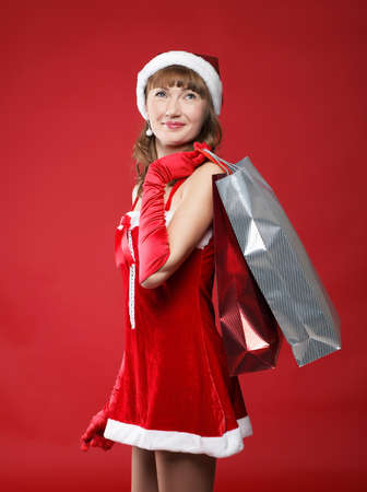 Portrait of a young charming girl dressed as Santa with a bag of shopping in their hands photo